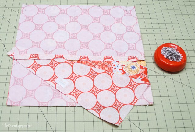 Fabric on cutting mat with other fabric on top to make pillow envelope closure