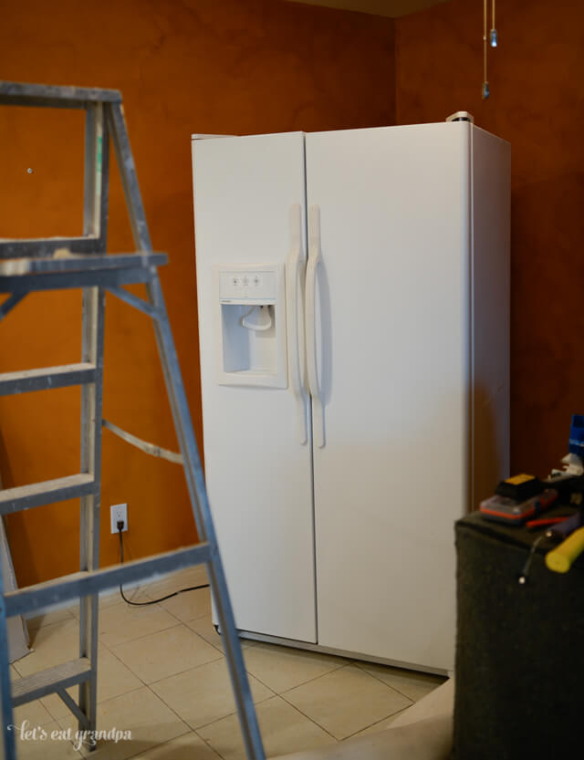 refrigerator in garage with lladder blcoking it