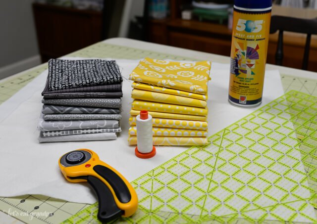 fabric, rotary cutter, and basting spray on cutting mat - supplies needed for QAYG tutorial