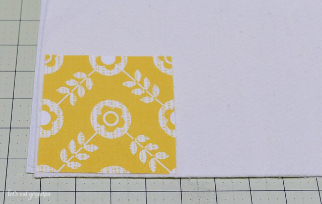 yellow square fabric to the corner of batting right side up