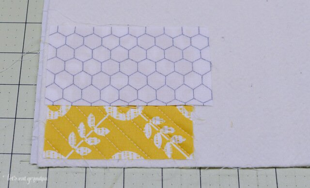 strip of fabric on each side of a fabric square on backing fabric