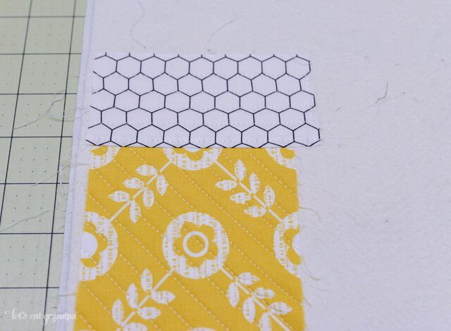 quilted fabric strip on each side of a fabric square on backing fabric