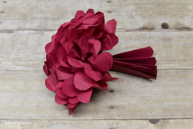 Fluffing a tissue paper flower. Tissue paper flowers make a gorgeous budget wedding centerpiece. Learn how to make four different types of tissue paper flowers!