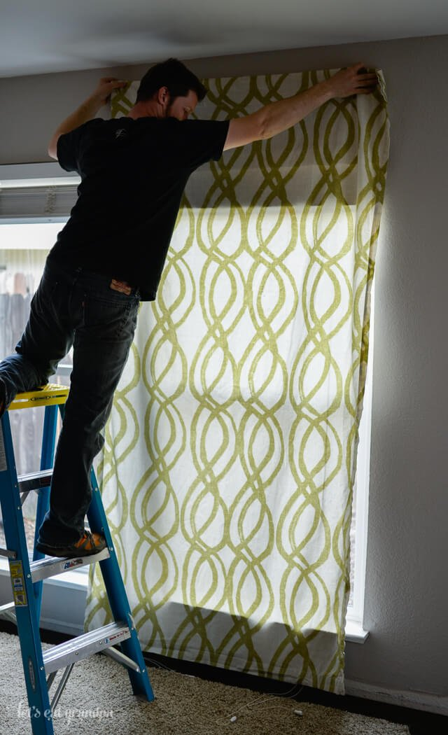 man standing on ladder to hang curtains