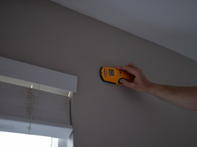 hand using stud finder to hang curtains