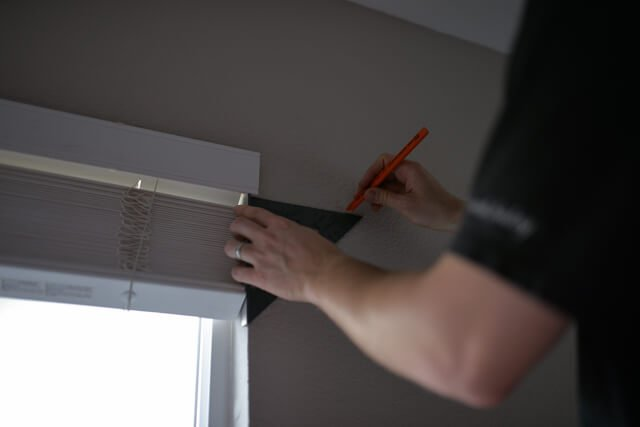 man measuring and marking spot with pencil where to hang curtains