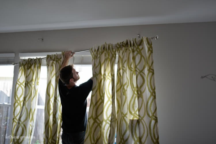 man holding curtain rod to hang curtains