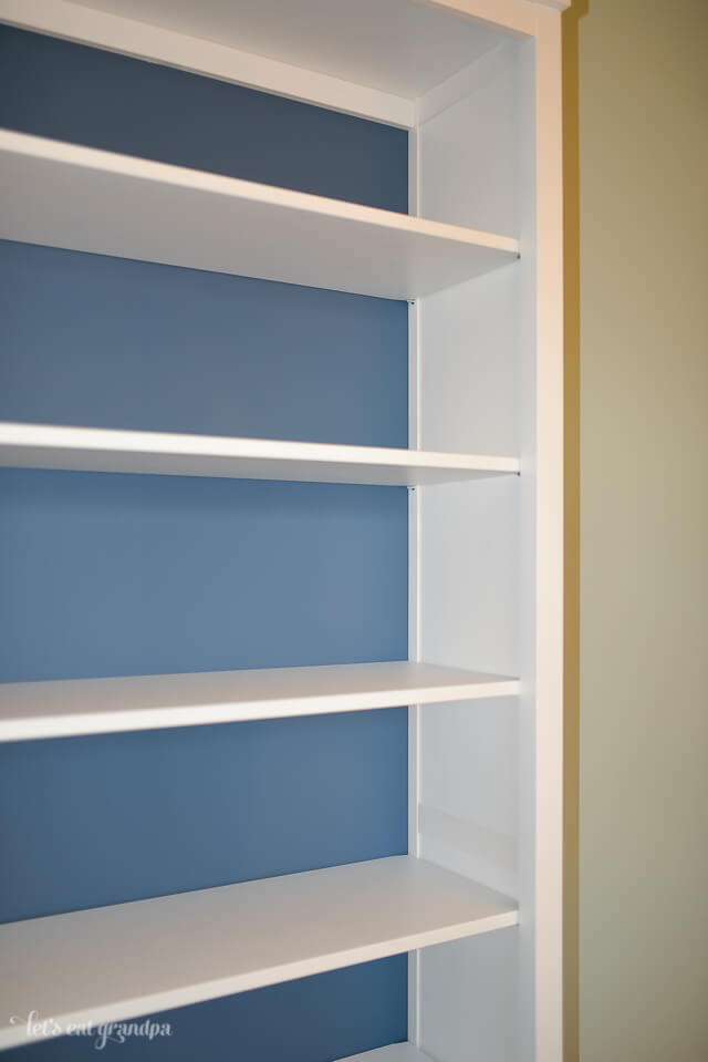 white bookshelf with blue back painted