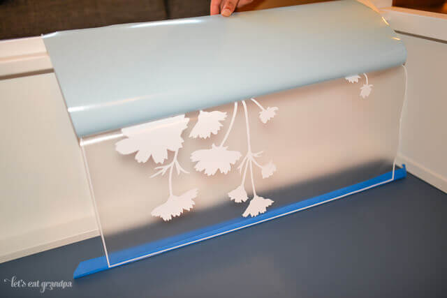 floral decal placed on bookshelf with blue tape