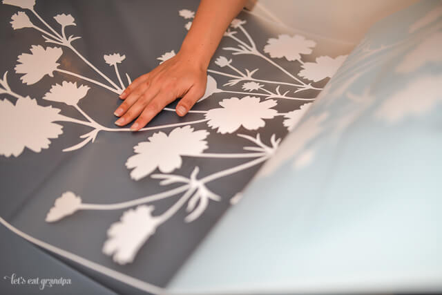 woman's hand placing floral decal on blue back of bookshelf