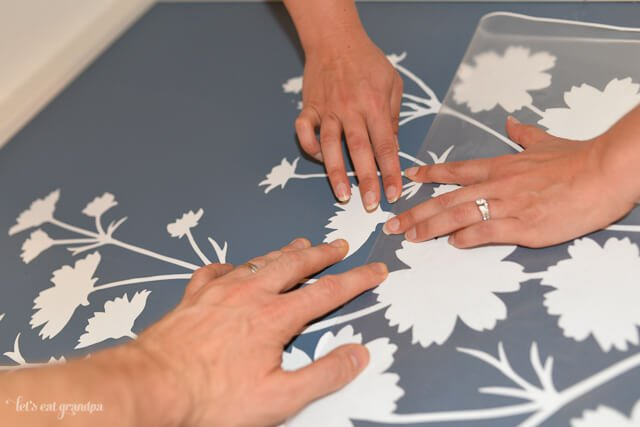 hands using credit card to stick wall decal on bookshelf