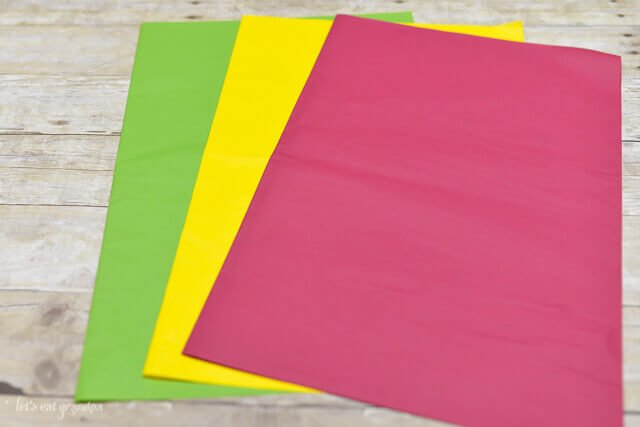 green, yellow, and magenta tissue paper sheets fanned out on wooden background