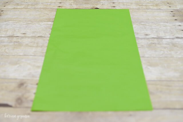 green tissue paper sheet on wooden background