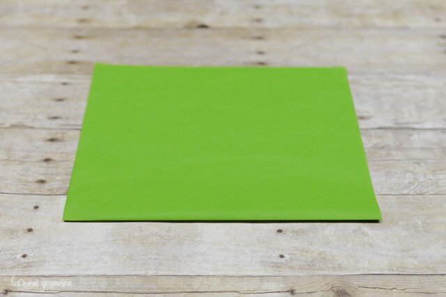 green tissue paper sheet on wooden background, horizontal