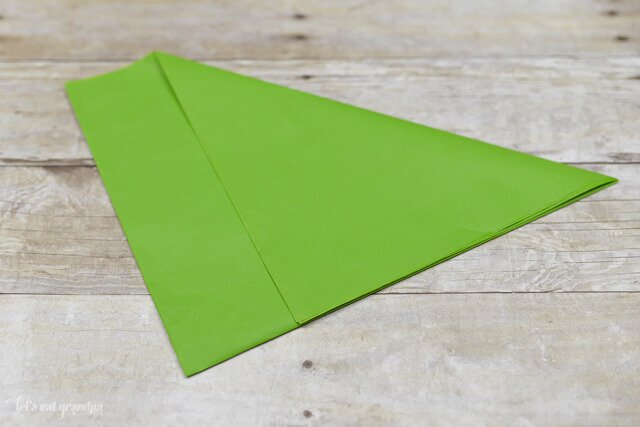 green tissue paper sheet on wooden background with corner folded over