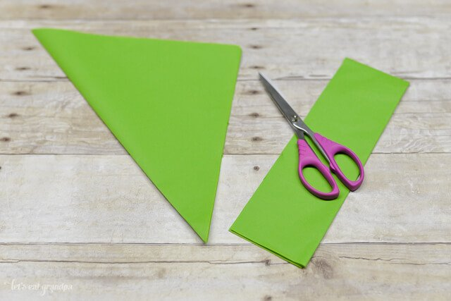 green tissue paper sheet on wooden background with folded corner side cut off