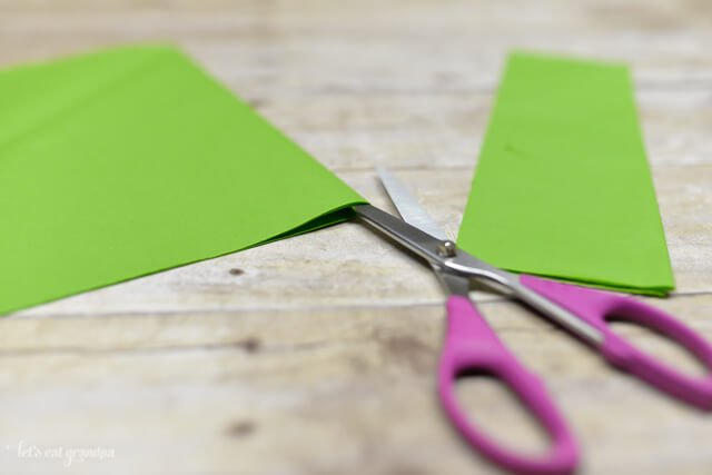 green tissue paper sheet on wooden background with corner cut off and scissors inserted in edge to cut