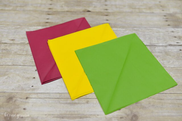 magenta, yellow, and green tissue paper sheet on wooden background, cut down to smaller squares