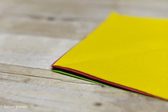 magenta, yellow, and green tissue paper sheet stacked on wooden background