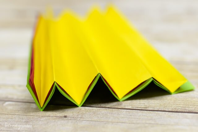 magenta, yellow, and green tissue paper sheet stacked and folded accordion on wooden background