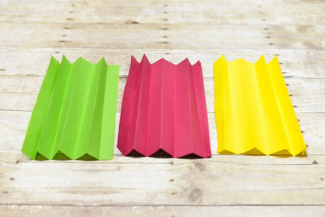 magenta, yellow, and green tissue paper sheet folded accordion style on wooden background