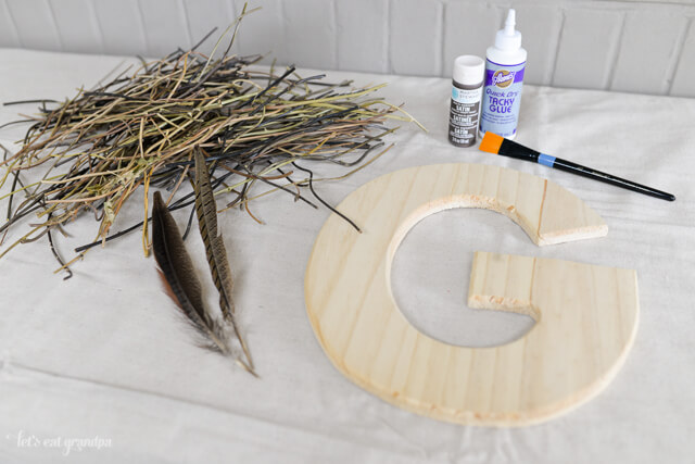 supplies needed to make found object initial - G letter, glue, paint, sticks, and feathers