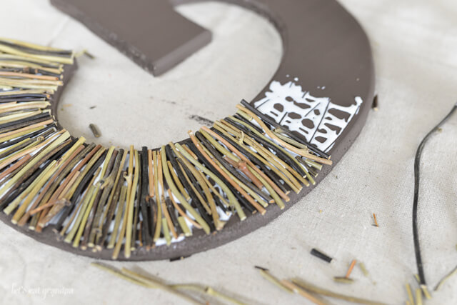 sticks being glued to brown G initial