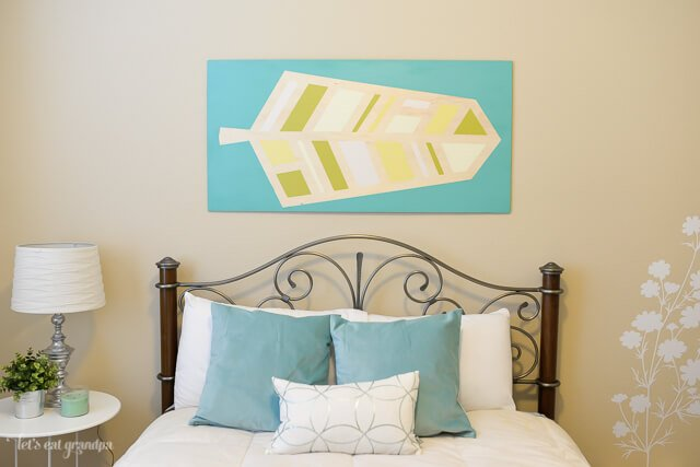 pretty bed in guest room makeover with wall art above bed