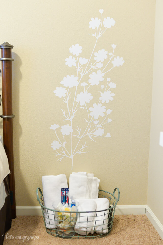 floral decal on wall with small basket of guest room necessities