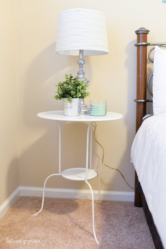 bedside table with lamp, small plant, and candle