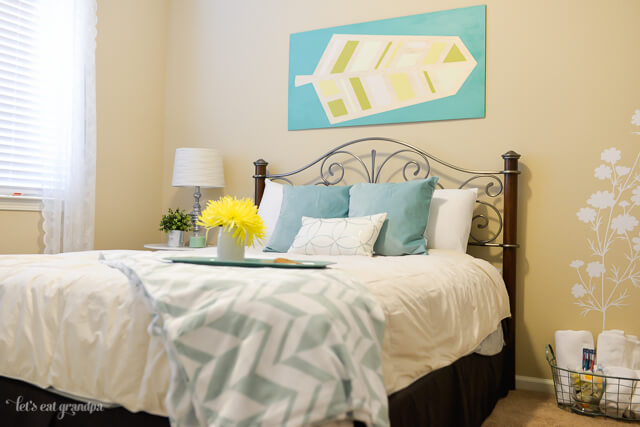 finished view of guest room makeover with bed and wall art