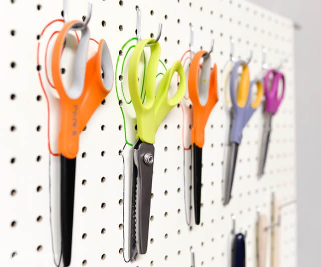 scissors hanging from pegboard with colorful sharpie outline behind them