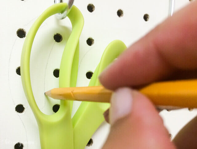 outlining scissor outline in pencil for pegboard