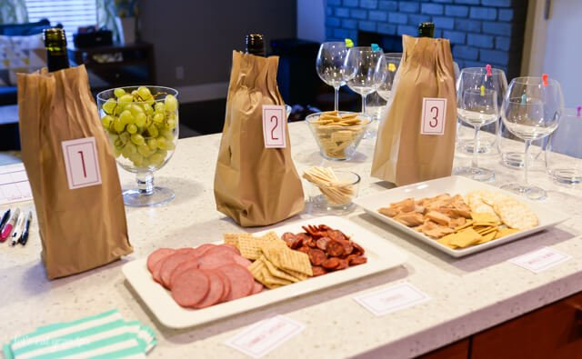 wine in brown bags with numbered labels and snack trays on counter