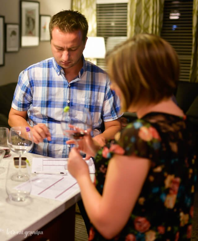 man and woman tasting wine and filling out wine sheets