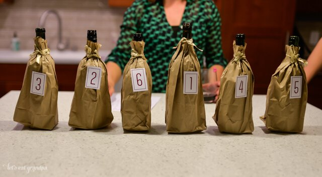 row of six red wines in brown bags with numbered labels on them
