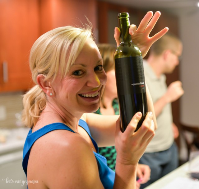 woman holding up bottle of red wine