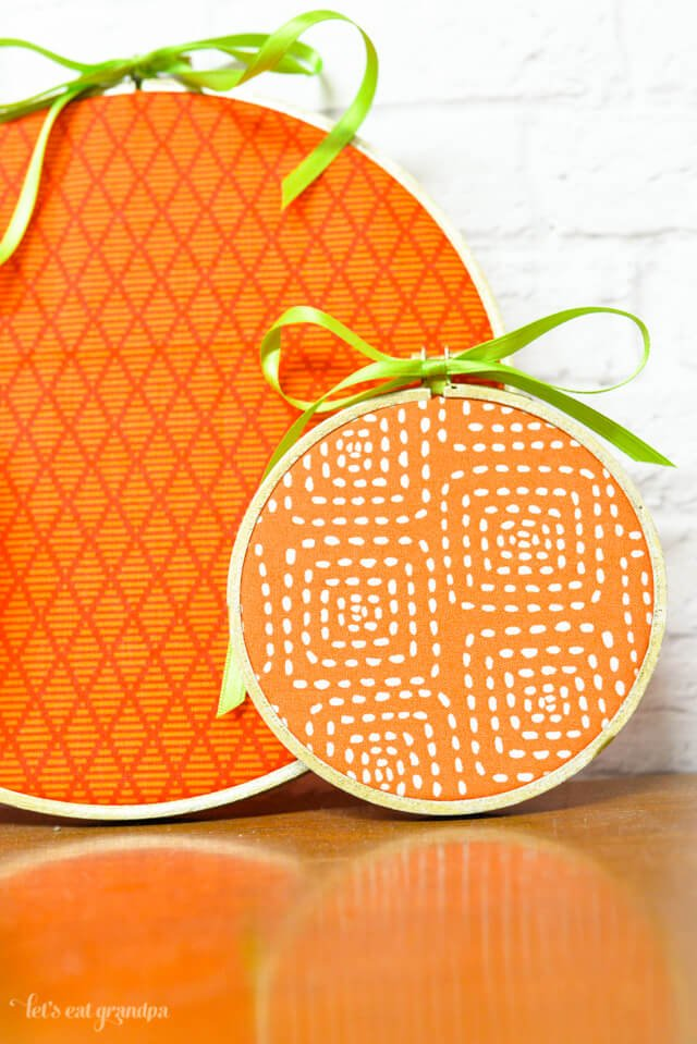 close up of two orange pumpkin embroidery hoops finished