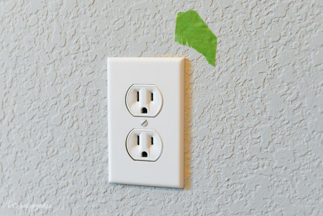 wall outlet with green painter's tape on wall