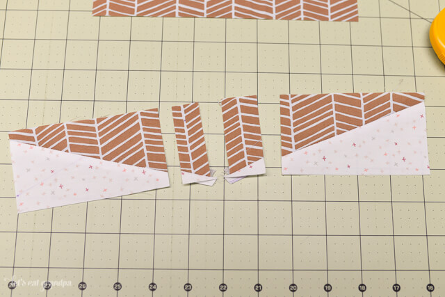 brown and white fabric pieces laid on sewing mat to make acorn block quilt pillow