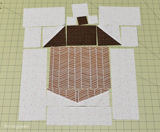 brown and white fabric pieces cut and laid on sewing mat to make acorn block quilt pillow