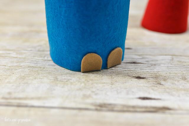tan felt pieces on bottom of blue felt to make christmas gnome's feet