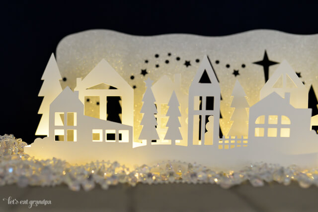 This gorgeous winter wonderland Christmas luminaria is a beautiful decoration on your Christmas mantel or table! Cut using your Cricut or other cutting machine and add fairy lights so it glows!