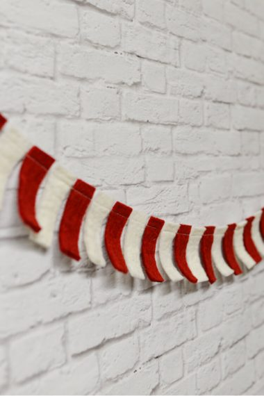 This festive Christmas candy cane garland takes just fifteen minutes and two colors of felt. Would be great for a Dr. Seuss Cat in the Hat party as well!