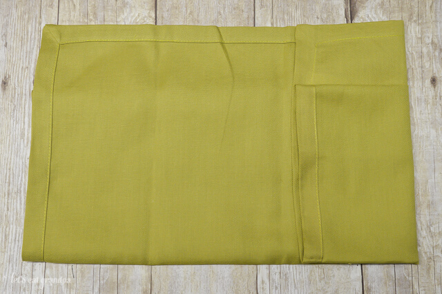 green napkin folded in half and one side folded in