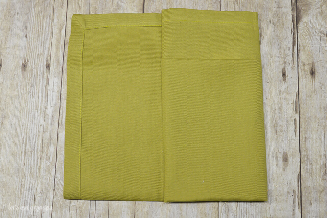 green napkin folded in half and one sided folded in