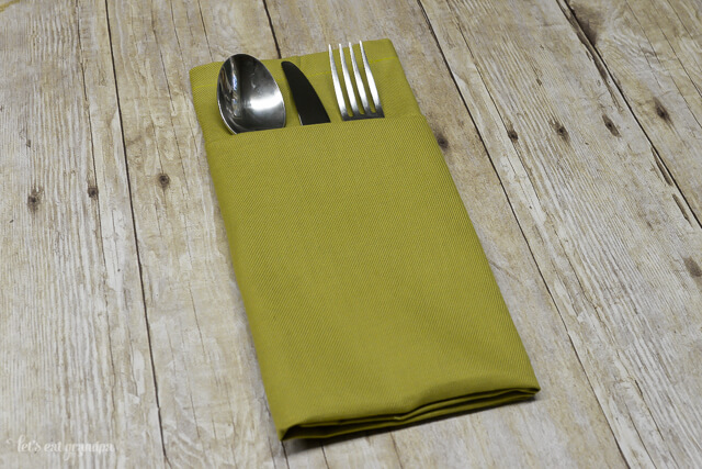 green napkin folded with a pocket and silverware inside