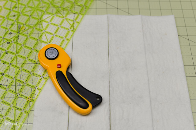 rotary cutter and strips of white felt