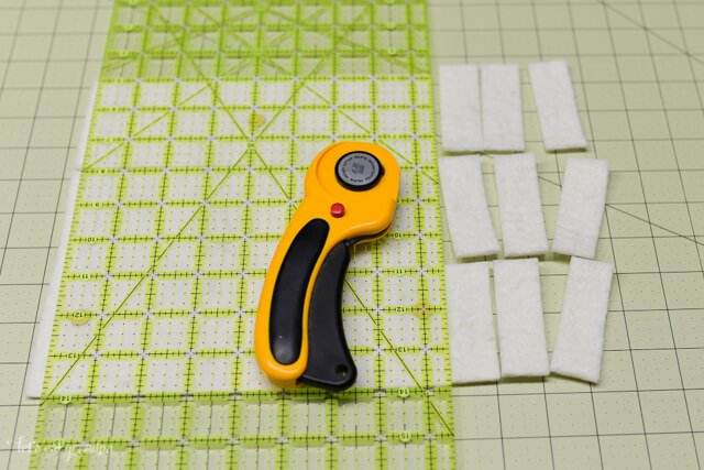 rotary cutter, cutting mat and strips of white felt cut