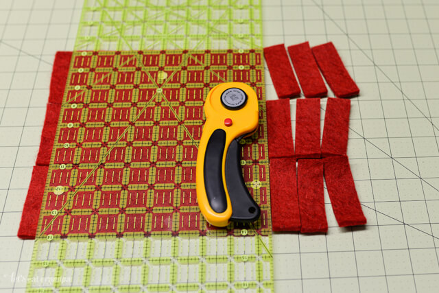 rotary cutter, cutting mat and strips of red felt cut